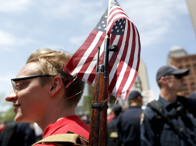 A protester legally brings a rifle into Public Square under Ohio's open carry law, Wednesday, July 20, 2016, in Cleveland, during the third day of the Republican convention. (Photo by John Minchillo/AP Photo)