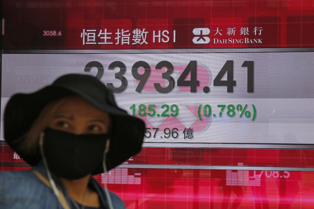 A woman wearing a face mask walks past an electronic board showing Hong Kong share index outside a local bank in Hong Kong, Tuesday, April 7, 2020. Asian shares are rising, echoing the rally on Wall Street fueled by signs of hope that the coronavirus pandemic could be slowing. (Photo by Kin Cheung/AP Photo)