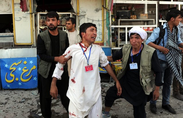 People helps an injured victim after a suicide bomb attack that targeted a demonstration of Hazara minority in Kabul, Afghanistan, 23 July 2016. (Photo by Hedayatullah Amid/EPA)