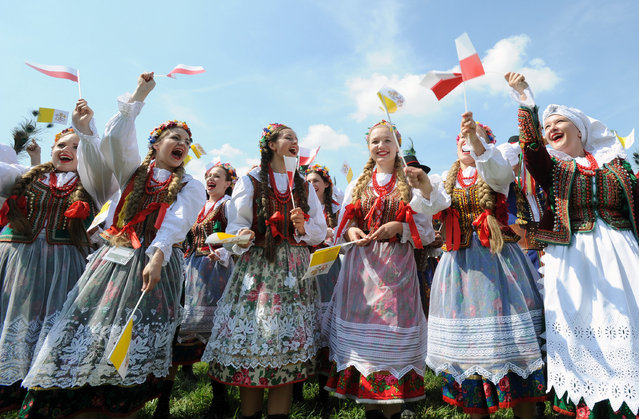 A group of folk dancers rehearse prior to the arrival of Pope Francis at the military airport in Krakow, Poland, Wednesday, July 27, 2016. Pope Francis is traveling to Poland to meet young Catholics from around the globe and visit the Auschwitz death camp and many Catholic places in this deeply religious nation. It will be the pope's first visit to central or Eastern Europe. (Photo by Alik Keplicz/AP Photo)
