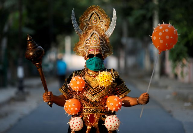 A local resident dressed as Yamraj or Hindu god of death, wearing a novel coronavirus-themed balloon necklace, gestures as he poses during an awareness about social distancing and staying at home organised by Delhi police during a nationwide lockdown to slow the spreading of the coronavirus disease (COVID-19), in New Delhi, India, April 28, 2020. (Photo by Adnan Abidi/Reuters)