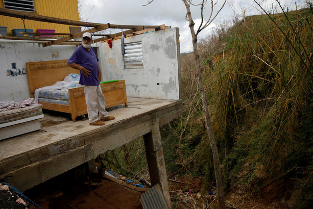 Roberto Morales Santos, 70, looks out after posing for a portrait in his home, damaged by Hurricane Maria, in the municipality of Barranquitas outside San Juan, Puerto Rico October 11, 2017. (Photo by Shannon Stapleton/Reuters)