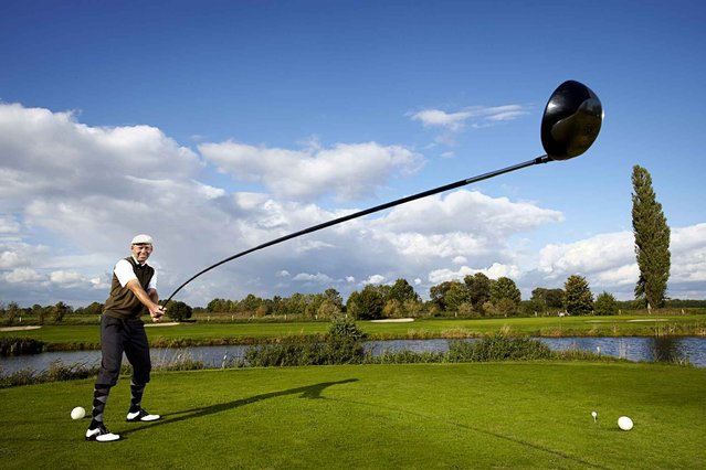 A recent undated handout picture released by the Guinness World Records on September 9, 2014, shows 49-year-old trick golf artist Karsten Maas, from Denmark, who secured his place in the 2015 Guinness World Records book for creating the world's longest usable golf club. It measures 4.37, (14ft 5in) in length and has been used to drive a ball a distance of 165.46m (542ft 10.16in). (Photo by Ranald Mackechnie/AFP Photo/Guinness World Records)