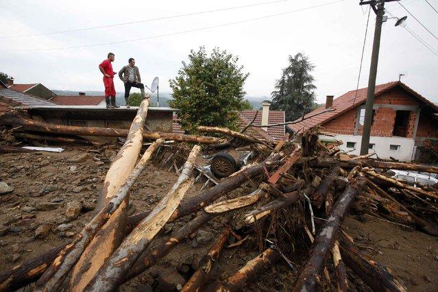 Two men inspect the damage produced by heavy floods in Tekija village September 17, 2014. (Photo by Djordje Kojadinovic/Reuters)