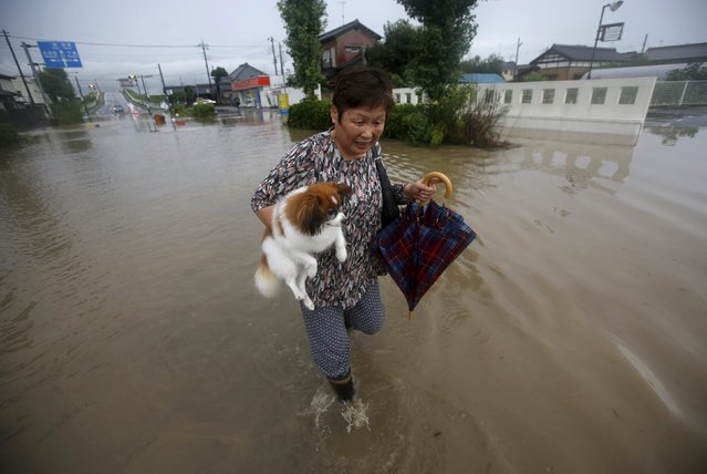 A woman holding her pet dog wades through a residential area flooded by the Kinugawa river, caused by typhoon Etau, in Joso, Ibaraki prefecture, Japan, September 10, 2015. (Photo by Issei Kato/Reuters)