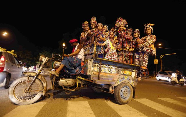 Dancers wearing traditional attires pose as they stand in a cart driven by a motorcycle on their way to perform Dandiya, a traditional dance, on the first day of the nine-day long Navratri festival in the western Indian city of Ahmedabad September 25, 2014. Navratri, held in honour of Hindu Goddess Durga, is celebrated over a period of nine days where thousands of youths dance the night away in traditional costumes. (Photo by Amit Dave/Reuters)