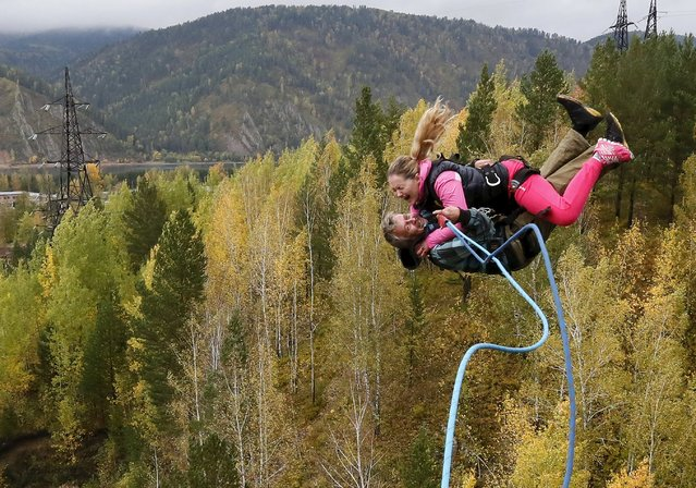 "Members of the ""Exit Point"" amateur rope-jumping group jump from a 44-metre high (144-ft) waterpipe bridge in the Siberian Taiga area outside Krasnoyarsk, September 13, 2015. Rope-jumping, an extreme sport, involves jumping from a high point using an advanced leverage system combining mountaineering and rope safety equipment. (Photo by Ilya Naymushin/Reuters)"