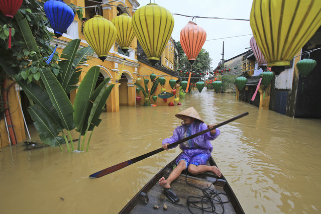 Nguyen Thi Vui paddles her boat in the flooded streets of Hoi An, Vietnam, Monday, November 6, 2017. (Photo by Hau Dinh/AP Photo)