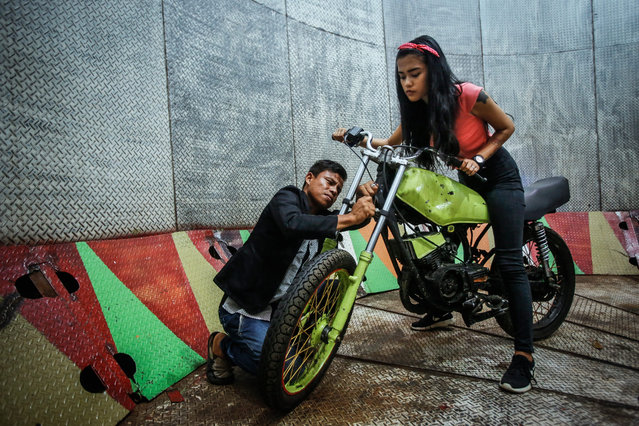 """A picture made available on 16 August 2016 shows a young dare devil motorbike rider, Karmila Purba, 18, and her mentor Tora Palevi checking her motorbike before the show time of """"Tong Setan"""" or Davil's Barrel show, at a traditional night carnival in Deliserdang, North Sumatra, Indonesia, 11 August 2016. (Photo by Dedi Sinuhaji/EPA)"""
