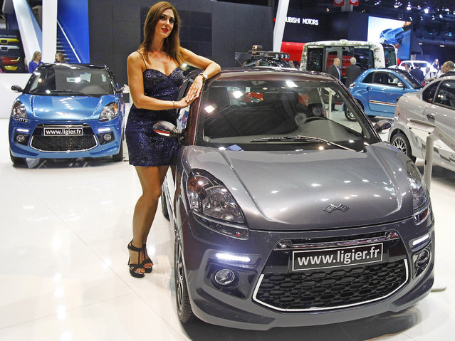 A hostess poses next to a car made by French manufacturer  Ligier, presented at the Paris Motor Show, in Paris, Thursday October 2, 2014. (Photo by Remy de la Mauviniere/AP Photo)