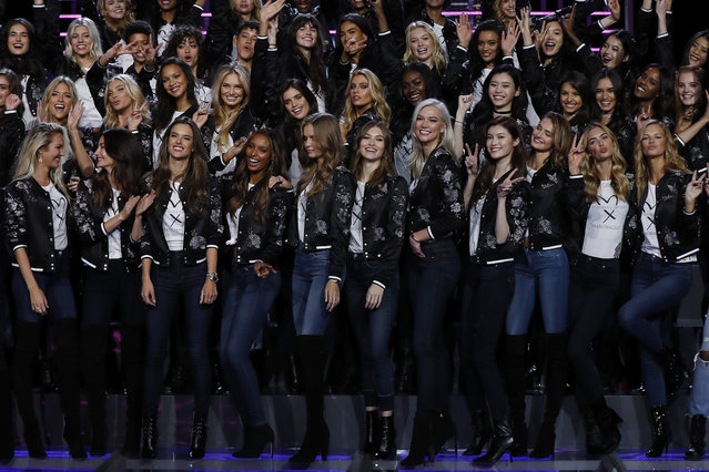 Models of the Victoria's Secret Fashion Show, some sharing light moment with each others as they pose for a group photo on stage at the Mercedes-Benz Arena in Shanghai, China, Saturday, November 18, 2017. (Photo by Andy Wong/AP Photo)