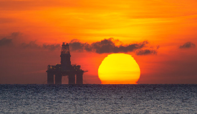 The sun rises behind a redundant oil platform moored off Kirkcaldy in Fife, Scotland on April 14, 2020, as oil prices remain under pressure. (Photo by Murdo MacLeod/The Guardian)