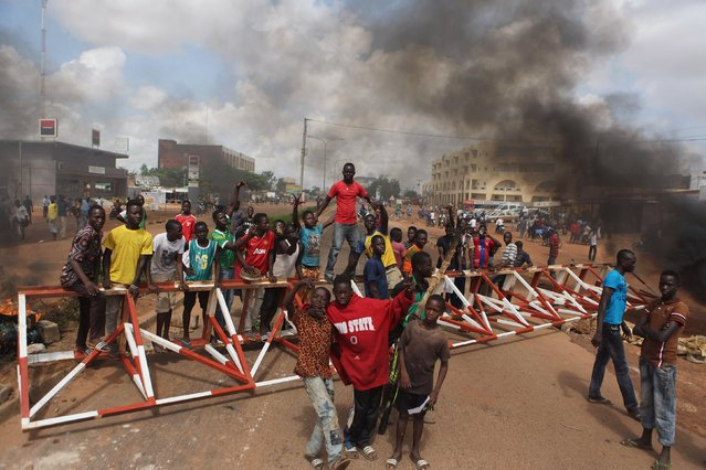 Anti-coup protesters gather at a barricade they set up in Ouagadougou, Burkina Faso, September 19, 2015. (Photo by Joe Penney/Reuters)