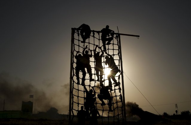 Palestinian militants from al-Husine brigade loyal to Fatah movement, climb a net during a military-style exercise graduation ceremony in Khan Younis in the southern Gaza Strip, September 20, 2015. (Photo by Suhaib Salem/Reuters)