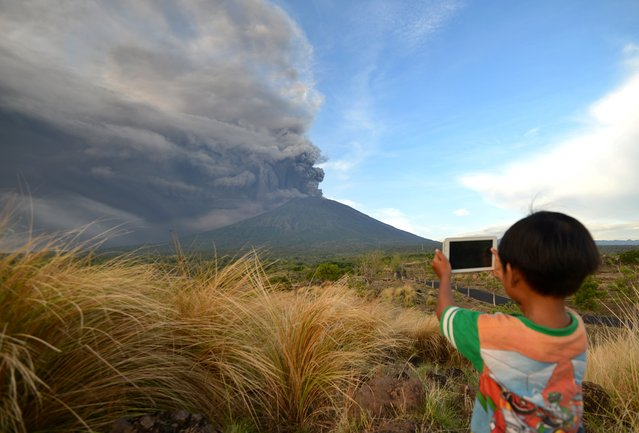 A boy takes pictures during Mount Agung's eruption seen from Kubu sub-district in Karangasem Regency on Indonesia's resort island of Bali on November 26, 2017. (Photo by Sonny Tumbelaka/AFP Photo)