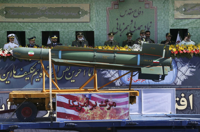 "Iranian armed forces commanders review weapons as an anti-U.S. banner which reads in Persian: ""death to America"" is placed on the truck in a military parade marking the 35th anniversary of Iraq's 1980 invasion of Iran, in front of the shrine of late revolutionary founder Ayatollah Khomeini, just outside Tehran, Iran, Tuesday, September 22, 2015. (Photo by Vahid Salemi/AP Photo)"