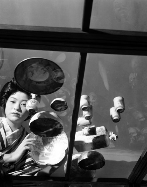 Kyoto has become the center of the Satsumaware industry. Part of the display case at the factory, in foreground a tea set with cake plates and in the background the girl looking at a demi-tasse set at the Kotobuki Pottery factory in Kyoto, Japan on September 23, 1948. (Photo by AP Photo)