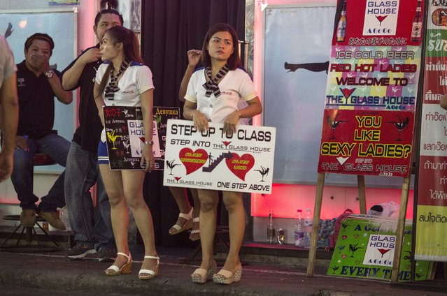 Bar girls hold signs to get customers along the Walking Street where bars and s*x scenes are a commonplace July 31, 2016 in Pattaya, Thailand. (Photo by Paula Bronstein/Getty Images)