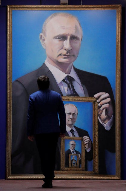 """A man looks at a painting depicting Russian president Vladimir Putin at the """"SUPERPUTIN"""" exhibition at UMAM museum in Moscow, Russia on December 6, 2017. (Photo by Maxim Shemetov/Reuters)"""