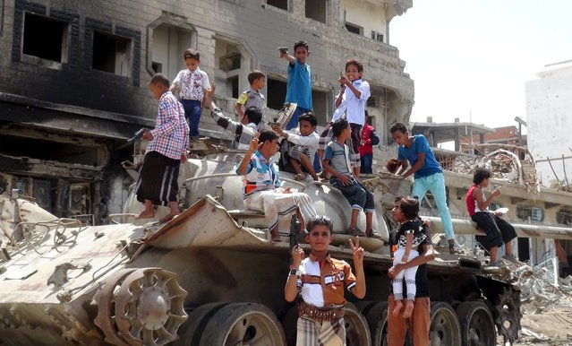 Boys hold toy weapons as they stand on a tank on a street during the first day of Eid al-Adha in Yemen's southern port city of Aden September 24, 2015. (Photo by Reuters/Stringer)