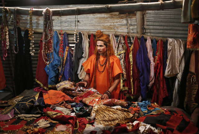 An artist looks for his garments in a pile of clothes as he gets ready backstage before performing during Ramlila, a re-enactment of the life of Lord Rama, ahead of Dussehra in New Delhi September 23, 2014. (Photo by Anindito Mukherjee/Reuters)