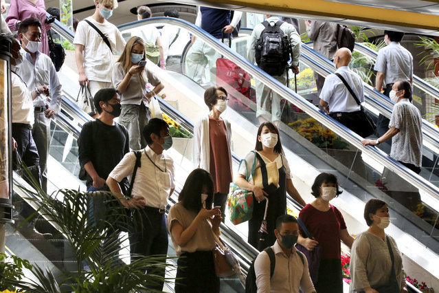 People wearing face masks to protect against the spread of the new coronavirus take an escalator at Yokohama station near Tokyo, Wednesday, July 22, 2020. (Photo by Koji Sasahara/AP Photo)