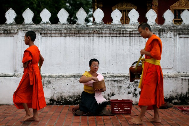 Buddhist monks walk while collecting alms early morning in front of Wat Sene Buddhist temple in Luang Prabang, Laos July 31, 2016. (Photo by Jorge Silva/Reuters)