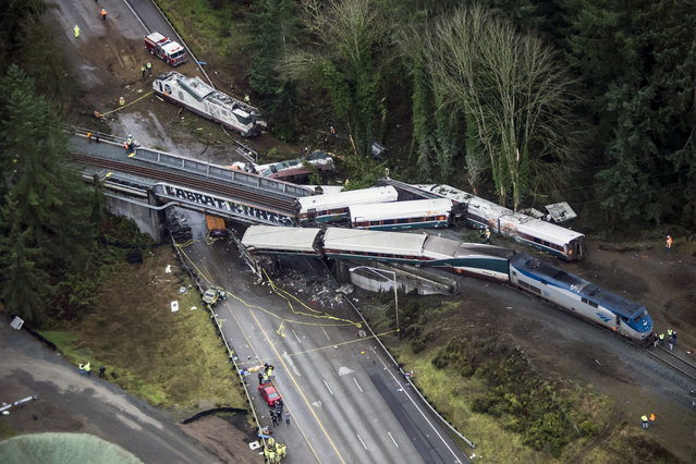 Cars from an Amtrak train that derailed lie spilled onto Interstate 5, Monday, December 18, 2017, in DuPont, Wash. The Amtrak train making the first-ever run along a faster new route hurtled off the overpass Monday near Tacoma and spilled some of its cars onto the highway below, killing several people, authorities said. (Photo by Bettina Hansen/The Seattle Times via AP Photo)