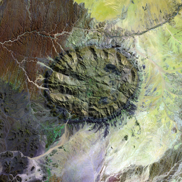 Over 120 million years ago, a single mass of granite punched through the Earth's crust and intruded into the heart of the Namib Desert in what is now northern Namibia. Today the mountain of rock called the Brandberg Massif towers over the arid desert below. A ring of dark, steep-sided rocks forced upward during the mountain's arrival encircles the granite intruder. Its volcanism has long since stilled, but the granite core left behind apparently glows red in the light of the setting sun. The formation is a remnant of a long period of tumultuous volcanic and geologic activity on Earth during which the southern super-continent of Gondwana was splitting apart. The mountain influences the local climate, drawing more rain to its flanks than the desert below receives. The rain filters into the mountain's deep crevices and slowly seeps out through springs. Unique plant and animal communities thrive in its high-altitude environment, and prehistoric cave paintings decorate walls hidden in the steep cliffs that gouge the mountain. To the southwest of Brandberg Massif, an older and more-eroded granite intrusion blends in subtly with the desert landscape, while along the Ugab River at upper left, cracks line the brown face of an ancient plain of rock transformed into gneiss by heat, pressure, and time. This image was acquired by Landsat 7's Enhanced Thematic Mapper plus (ETM+) sensor. (Photo by NASA/GSFC/USGS EROS Data Center)