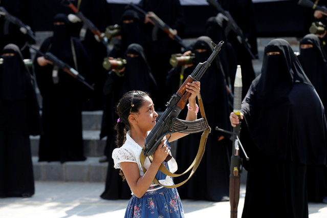 A girl holds a rifle in front of women loyal to the Houthi movement taking part in a parade to show support to the movement in Sanaa, Yemen September 6, 2016. (Photo by Khaled Abdullah/Reuters)