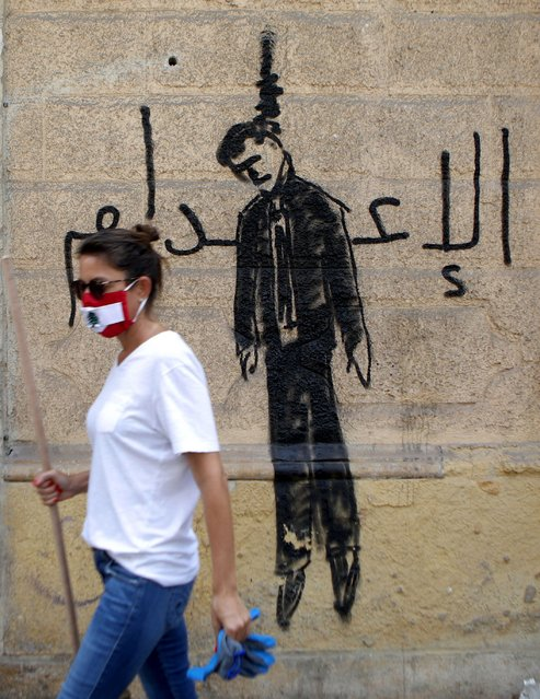 A member of the Lebanese civil society carrying a broom used for clearing debris, walks past a wall painting depicting a hanged politician and reading (death sentence in Arabic) in the partially damaged Beirut neighbourhood of Mar Mikhael on August 7, 2020. (Photo by Patrick Baz/AFP Photo)