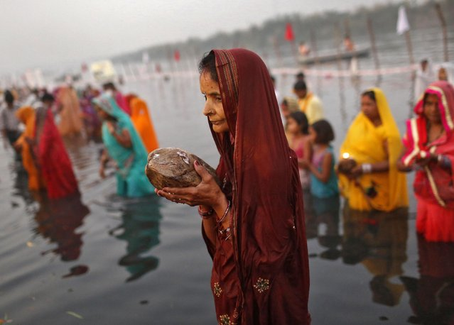 Hindu women worship the Sun god Surya in the waters of the river Yamuna during the Hindu religious festival of Chatt Puja in New Delhi October 30, 2014. (Photo by Anindito Mukherjee/Reuters)