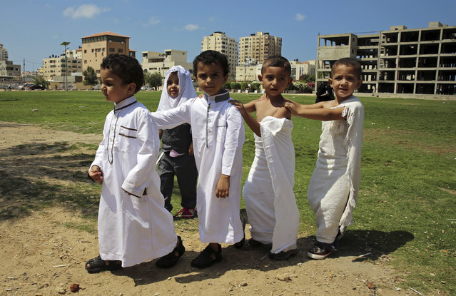 Palestinian students dressed like Muslim pilgrims walk together during a school lesson about the hajj pilgrimage to Mecca, Saudi Arabia, at the main square in Gaza City, Thursday, September 8, 2016. Millions of Muslims have arrived in Saudi Arabia to participate in the annual hajj pilgrimage, which starts Saturday, a ritual required of all able-bodied Muslims at least once in their life. (Photo by Adel Hana/AP Photo)