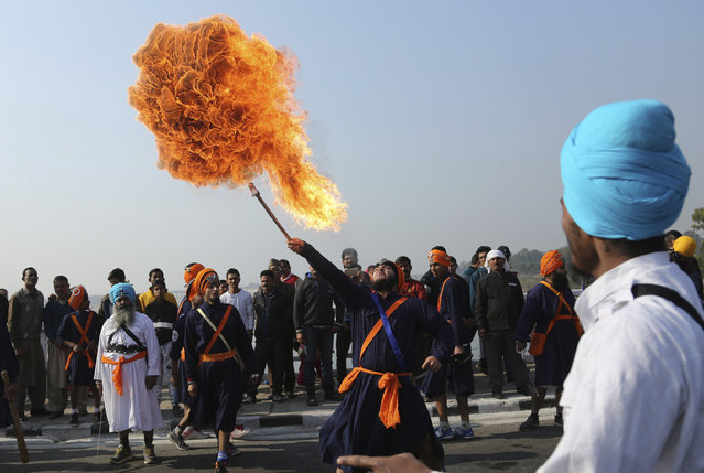 An Indian Sikh warrior performs a fire act as he displays traditional martial art skills during a religious procession ahead of the birth anniversary of Guru Gobind Singh in Jammu, India, Tuesday, January 2, 2018. Guru Gobind Singh, was the tenth Sikh guru. (Photo by Channi Anand/AP Photo)