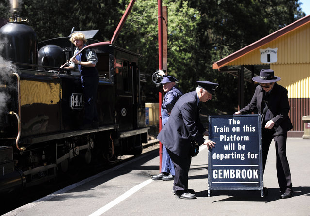 Staff at the Puffing Billy railway station of Lakeside put out a sign for the next arriving train as locomotive 14A is watered on the platform near Melbourne, October 20, 2014. (Photo by Jason Reed/Reuters)