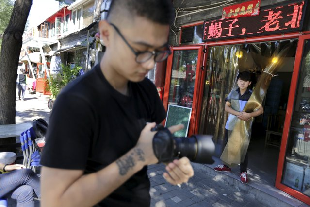 Chinese artist ROBBBB prepares to take pictures of people along a street for his artworks in Beijing's Gulou area, September 25, 2015. The 25-year-old artist in Beijing prefers to display his work on the walls of abandoned buildings, rather than a gallery. His artwork is mostly derived from photos of people he sees in the Chinese capital, anyone ranging from elderly people to construction workers. (Photo by Jason Lee/Reuters)
