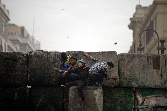 Skirmishes break out between protesters and security forces, unseen, near Tahrir Square, on January 25, 2013. (Photo by Khalil Hamra/AP Photo/The Atlantic)