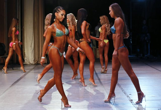 "Participants of the bikini fitness competition perform during the 5th ""Strongo Cup"" open amateur tournament at the State Opera and Ballet Theatre in Russia's Siberian city of Krasnoyarsk, November 1, 2014. (Photo by Ilya Naymushin/Reuters)"
