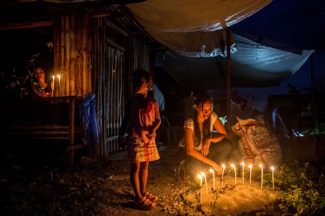 A family lights candles outside their temporary home in San Jose during the candlelight memorial on November 8, 2014 in Tacloban, Leyte, Philippines. People lined the roads with candles all across Tacloban from the airport to downtown in remembrance of the victims of Typhoon Haiyan. (Photo by Chris McGrath/Getty Images)
