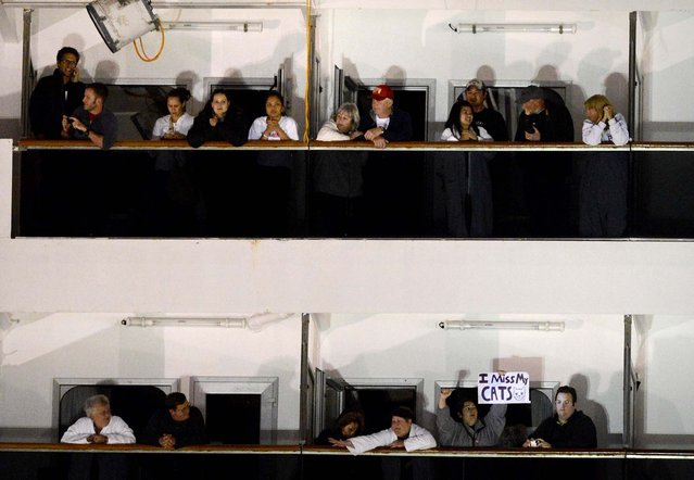 People watch from their balconies aboard the Carnival Triumph after it was towed to the cruise terminal in Mobile, February 14, 2013. (Photo by John David Mercer/Associated Press)