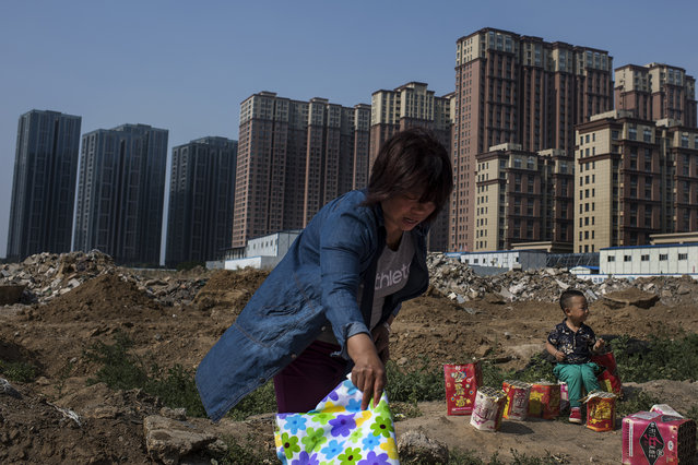 A woman lays out a blanket in front of a massive new housing development in the city of Yanjiao on May 21, 2016. Yanjiao, with a population of over 700,000 is a satellite city of Beijing that is rapidly consuming all of the villages surrounding it. (Photo by Michael Robinson Chavez/The Washington Post)