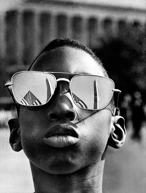 In this August 28, 1963 file photo, the top of the Washington Monument and part of a U.S. flag are reflected in the sunglasses of Austin Clinton Brown, 9, of Gainesville, Ga., as he poses at the Capitol where he joins others in the March on Washington. (Photo by AFP Photo)