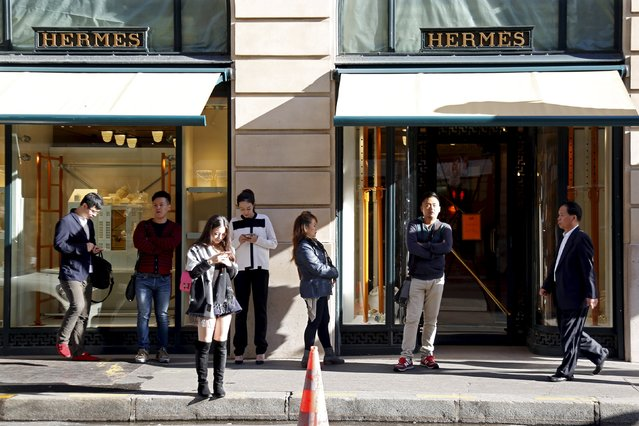 Customers queue up as they wait the opening of the main shop of French luxury group Hermes in Paris, France, September 23, 2015. Chinese luxury consumers are spending more on ready-to-wear and new labels, a notable shift in the behaviour and tastes of the world's top spenders, a Reuters survey of retailers in the United States, Asia and Europe showed. (Photo by Charles Platiau/Reuters)