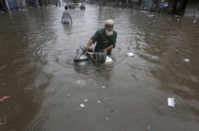 A cyclist navigates through a flooded road after heavy monsoon rains, in Lahore, Pakistan, Friday, September 4, 2020. Flash floods triggered by week-long monsoon rains that have hit northwestern Pakistan, including the scenic Swat Valley, killing dozens a government spokesman said. (Photo by K.M. Chaudary/AP Photo)