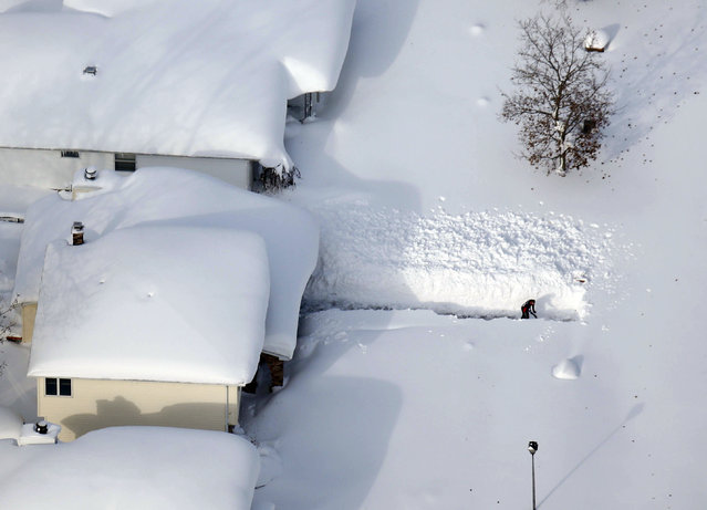 A man digs out his driveway in Depew, N.Y.,Wednesday, November 19, 2014. The Buffalo area found itself buried under as much as 5½ feet of snow Wednesday, with another lake-effect storm expected to bring 2 to 3 more feet by late Thursday. (Photo by Derek Gee/AP Photo/The Buffalo News)