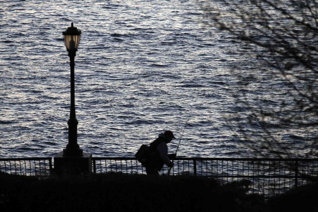 A fisherman packs up and leaves Battery Park at sunset after fishing on the Hudson River in New York November 15, 2014. (Photo by John Schults/Reuters)
