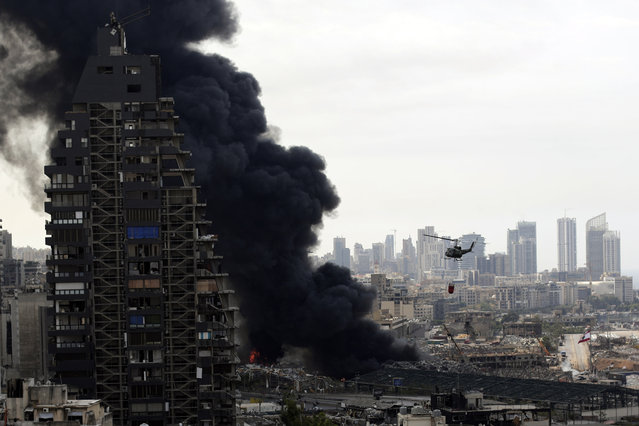 An army helicopter drops water on a fire at warehouses at the seaport in Beirut, Lebanon, Thursday, September 10. 2020. (Photo by Hassan Ammar/AP Photo)