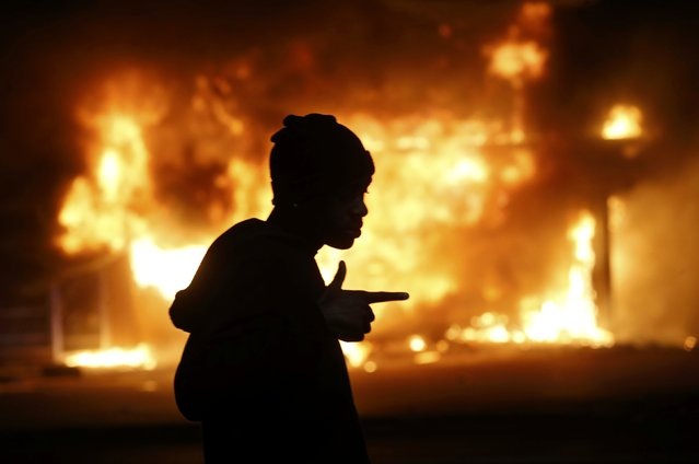 A man walks past a burning building during rioting after a grand jury returned no indictment in the shooting of Michael Brown in Ferguson, Missouri November 24, 2014. (Photo by Jim Young/Reuters)