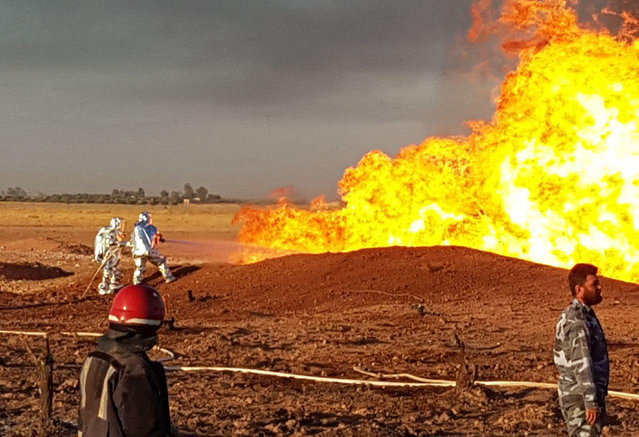 In this photo released by the Syrian official news agency SANA, Syrian firefighters extinguish the flames of a gas pipeline that hit by an explosion, between the northeastern Damascus suburbs of Adra and Dumair, in Syria Monday, August 24, 2020. An explosion early on Monday struck a gas pipeline in a Damascus suburb, cutting electricity throughout Syria, state media reported, citing the country's electricity and oil ministers. (Photo by SANA via AP Photo)
