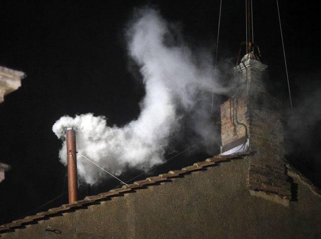 White smoke emerges from the chimney on the roof of the Sistine Chapel, in St. Peter's Square at the Vatican, Wednesday, March 13, 2013. The white smoke indicates that the new pope has been elected. (Photo by Gregorio Borgia/AP Photo)
